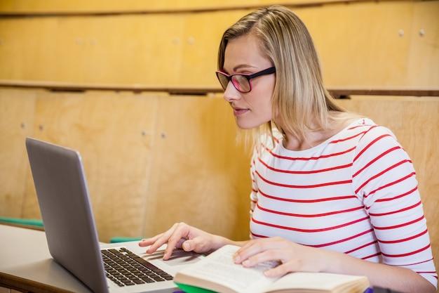 Estudiante feliz que usa el ordenador portátil y leyendo en la universidad