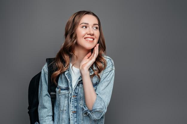 La estudiante feliz ríe y sonríe y parece lejos aislada sobre la pared gris. feliz, viaje, niña