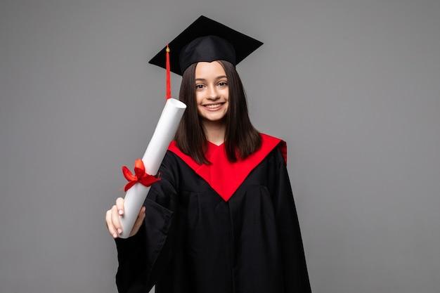 Estudiante feliz con sombrero de graduación y diploma en gris