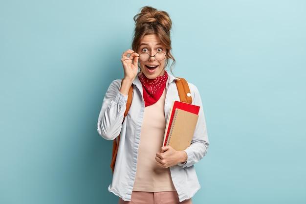 Estudiante feliz sorprendida mira a través de gafas, sostiene la mano en el marco, lleva cuaderno de espiral y libro rojo