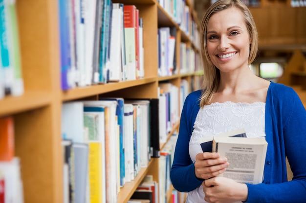 Estudiante feliz tomando libros en la biblioteca de la universidad