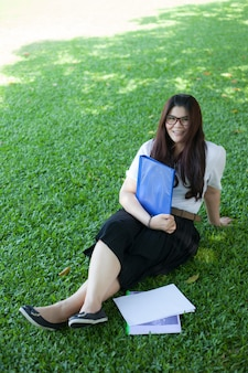 Estudiante femenina sentada en el césped