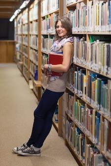 Estudiante femenino apoyado contra la estantería en la biblioteca