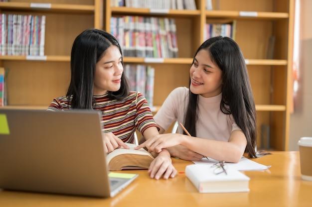 Estudiante femenino lee un libro en la biblioteca