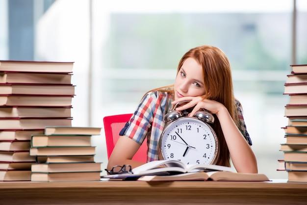 Estudiante femenino con el reloj que se prepara para los exámenes