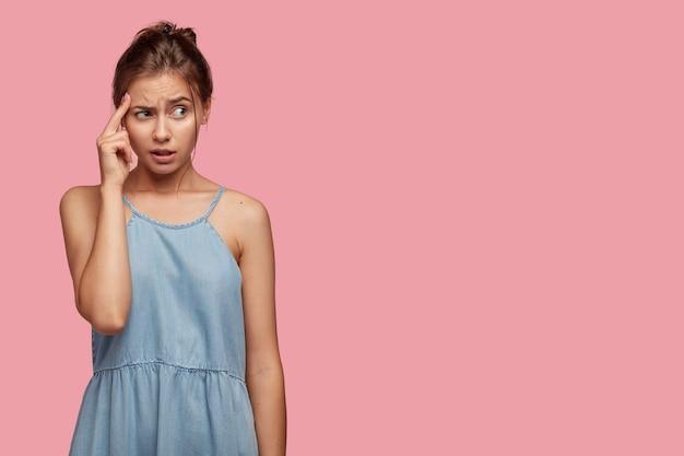 Estudiante frustrado mantiene el dedo en la sien, frunce el ceño con disgusto, trata de encontrar una solución en la mente, reflexiona sobre cómo resolver el problema, usa un vestido de mezclilla, modela sobre una pared rosa con espacio para copiar a un lado