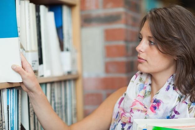 Estudiante de gemale que selecciona el libro del estante en biblioteca
