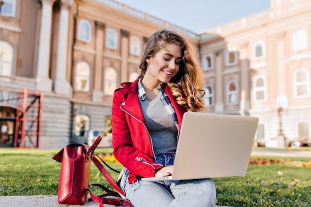 Estudiante glamorosa en chaqueta roja sentada en el patio frente a la universidad con computadora