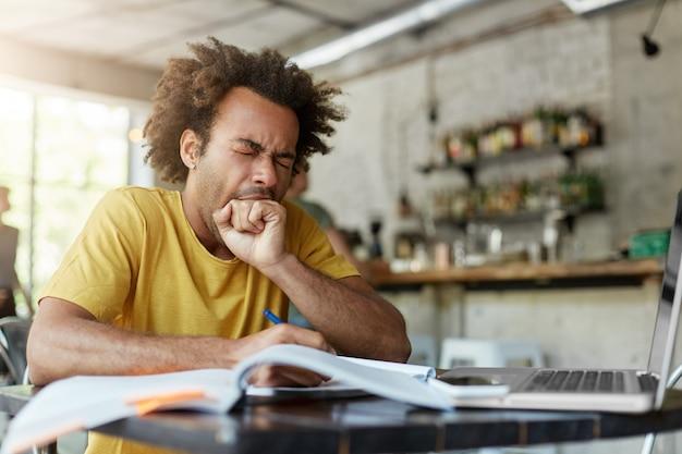 Estudiante graduado europeo negro soñoliento agotado bostezando, cubriendo la boca con el puño sintiéndose cansado