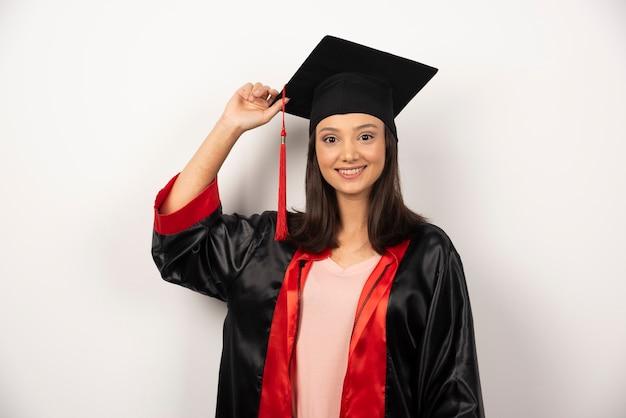 Estudiante graduado feliz en vestido posando sobre fondo blanco.