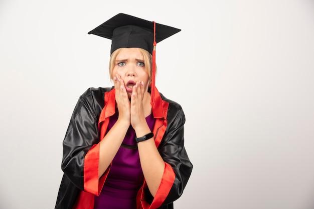 Estudiante graduado joven que se siente consternado sobre fondo blanco. foto de alta calidad