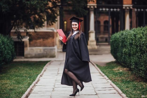 Estudiante graduado está de pie en el pasillo de la universidad en el manto, sonriendo y mirando a la cámara.
