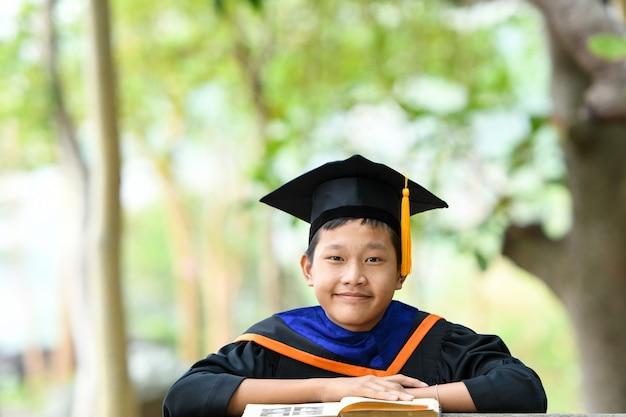 Un estudiante graduado sentado y leyendo un libro.