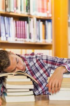Estudiante guapo agotado descansando la cabeza en pilas de libros