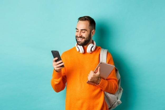 Estudiante guapo con auriculares y mochila, sosteniendo la tableta digital, leyendo el mensaje en el teléfono móvil, de pie contra el fondo azul claro.