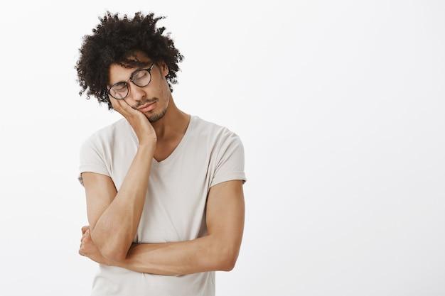 Estudiante guapo soñoliento que parece cansado, acostado en la palma y tomando la siesta