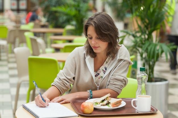Estudiante haciendo la tarea mientras tomaba el desayuno en el café