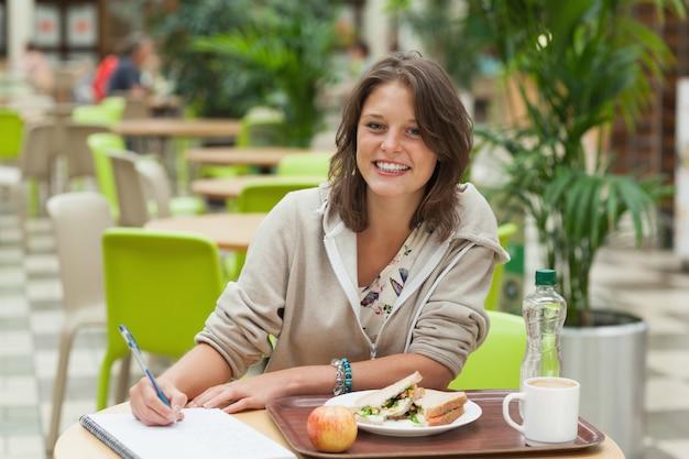 Estudiante haciendo la tarea mientras tomaba el desayuno en la cafetería