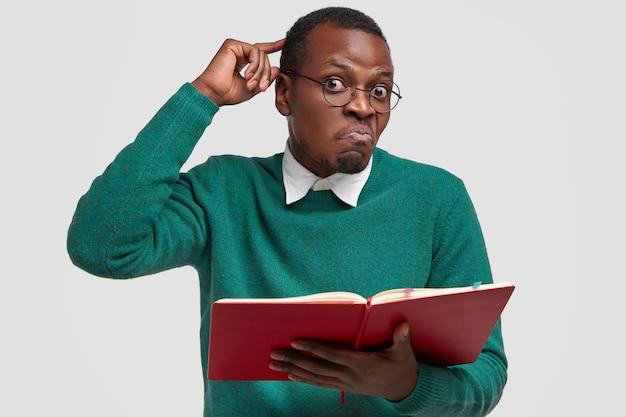 Un estudiante de hister negro confundido y perplejo se rasca la cabeza, pone los labios en la boca, no puede recordar material, abarrota la información del libro, vestido con un traje verde