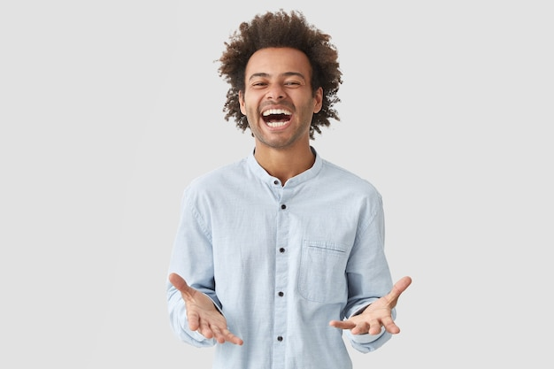 El estudiante hombre atractivo alegre lleno de alegría abre la boca ampliamente, se ríe con alegría, expresa positividad, vestido con una camisa elegante