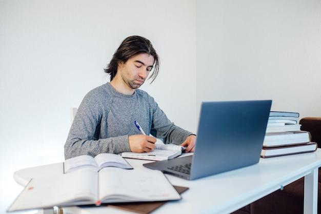 Estudiante hombre escribe en el cuaderno trabajando en equipo. marketing en internet, trabajo independiente, trabajo desde casa, aprendizaje en línea, estudio, concepto de bloqueo. educación a distancia, libros sobre la mesa