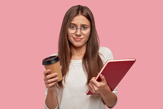 Estudiante infeliz disgustado mira con disgusto, frunce el ceño, usa lentes ópticos, lleva libros de texto y bebidas calientes, aislado sobre una pared rosa, no quiere estudiar. preparación para el examen.