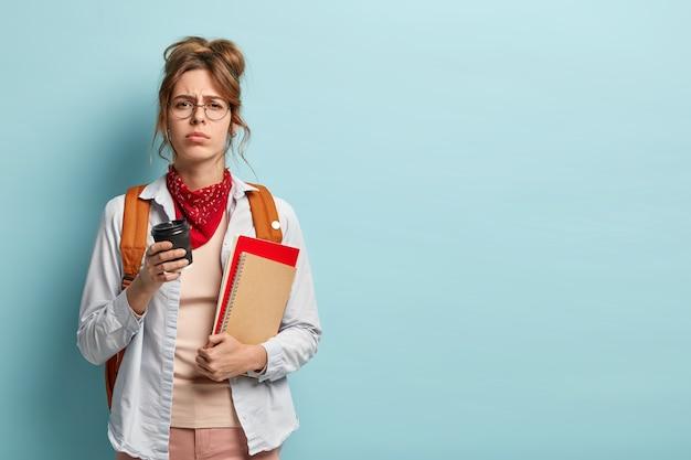 Estudiante insatisfecho con sueño posa con libros, bloc de notas y café, se siente con exceso de trabajo preparándose para el examen
