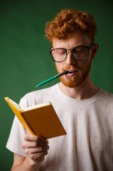 Estudiante inteligente de cabeza lectora con gafas con bolígrafo en la boca, sosteniendo el cuaderno