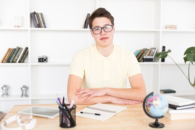 Estudiante inteligente en copas sentado en el escritorio