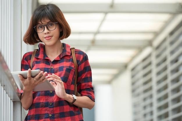 Estudiante inteligente con gafas usando la aplicación móvil en el teclado digital