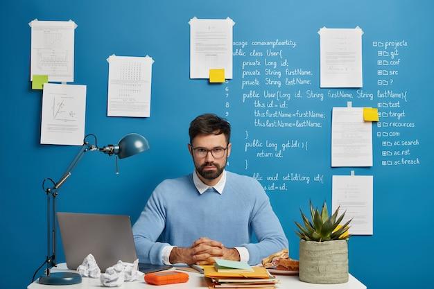 Estudiante inteligente y serio de la facultad de ti se sienta en un lugar de trabajo moderno