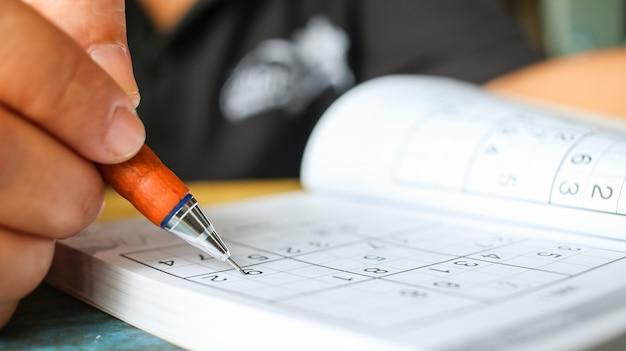 El estudiante está intentando resolver sudoku con el lápiz del color como afición en al aire libre