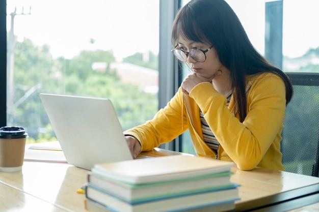 Estudiante joven del collage que usa la computadora y el dispositivo móvil que estudian en línea.