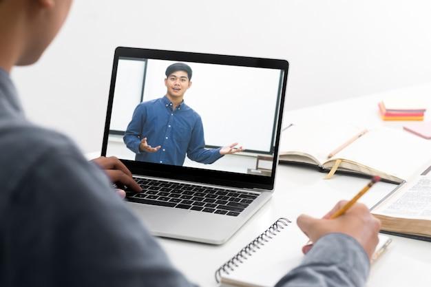 Estudiante joven del collage que usa la computadora que estudia en línea. educación y aprendizaje en línea.