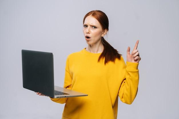 Estudiante joven enojado sosteniendo la computadora portátil y apuntando con el dedo hacia arriba sin mostrar ningún gesto