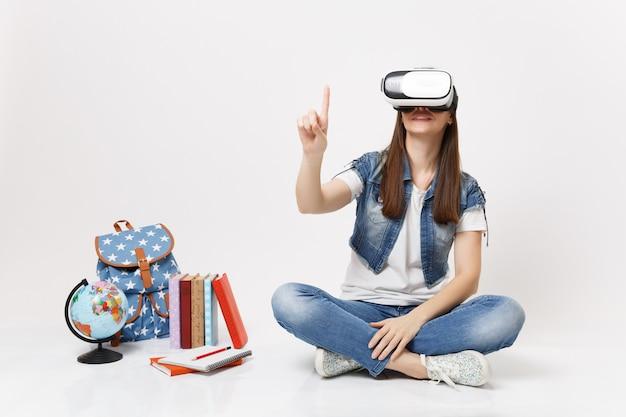 Estudiante joven en gafas de realidad virtual toca algo como presionar el botón, apuntando a la pantalla virtual flotante cerca del libro escolar de la mochila del globo aislado