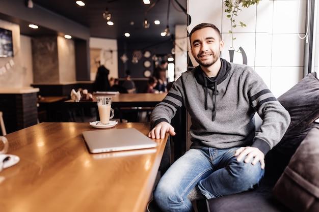 Estudiante joven con ordenador portátil beber café en la cafetería