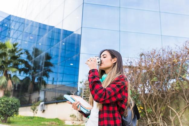 Estudiante joven que sostiene los libros en la mano que bebe el café