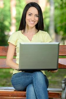 Estudiante joven que usa la computadora portátil al aire libre en parque