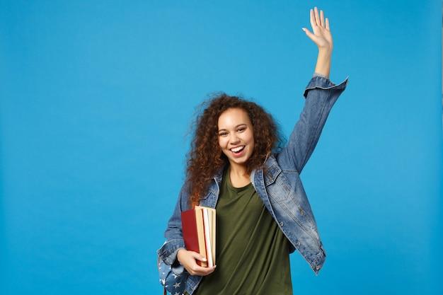 Estudiante joven en ropa de mezclilla y mochila tiene libros aislados en la pared azul