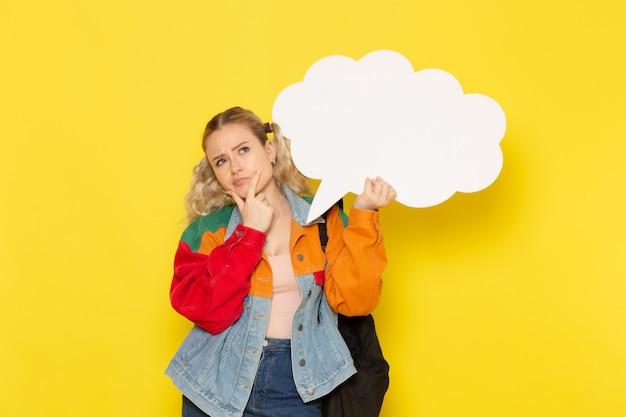 Estudiante joven en ropa moderna sosteniendo un enorme cartel blanco pensando en amarillo