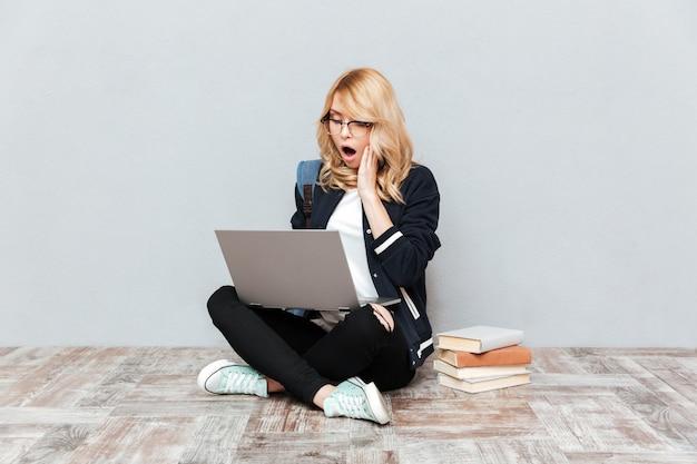 Estudiante joven sorprendido usando la computadora portátil.