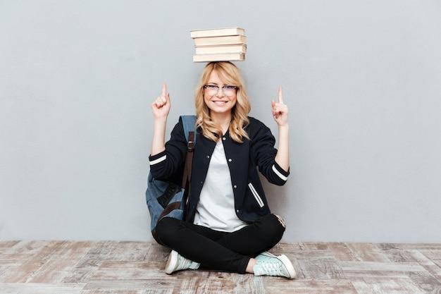 Estudiante joven sosteniendo libros sobre la cabeza y señalando