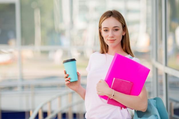 Estudiante joven con una taza de café en la calle