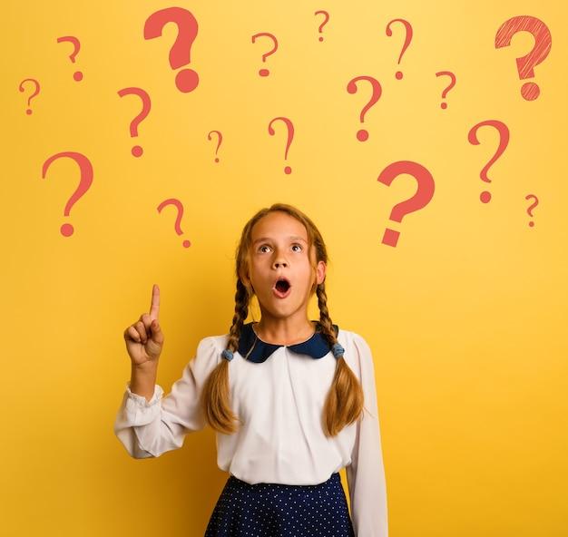 El estudiante joven tiene una expresión de asombro e indica muchos signos de interrogación. fondo amarillo