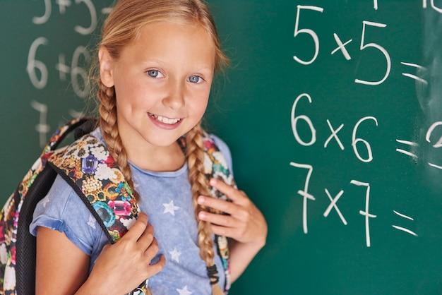 Estudiante junto a la pizarra con números.