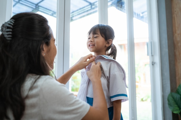 Estudiante de kindergarten vistiendo uniforme escolar en la mañana en casa