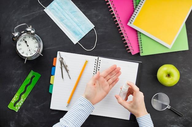 Estudiante laico plano con desinfectante encima del escritorio