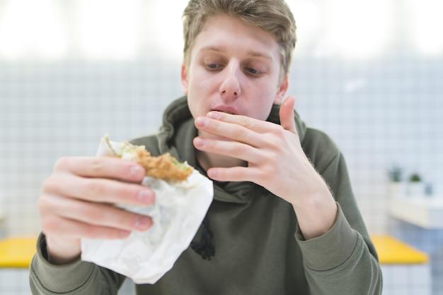 El estudiante se lame los dedos y se ve hambriento mirando la silla en sus manos.