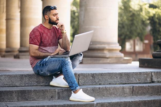 Estudiante con laptop por la universidad